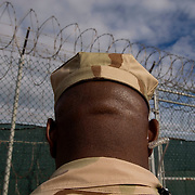 "A camp guard outside Camp 4 at the detention facility in Guantanamo Bay, Cuba. Camp 4 is a communal style camp where more compliant detainees live in small groups and have access to a more open air environment. Approximately 250 ""unlawful enemy combatants"" captured since the September 11, attacks on the United States continue to be held at the detention facility.(Image reviewed by military official prior to transmission)."