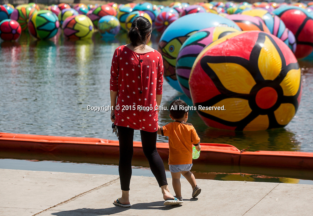 People walk past the hand-painted vinyl balls floating in the MacArthur Park Lake as part of a large-scale public arts installation organized by the Portraits of Hope charity in Los Angeles, California on August 26, 2015. The work titled ``The Spheres at MacArthur Park,'' involves filling the park's 8.39-acre lake with about 3,000 balls, each 4 to 6 feet in diameter and covered in bright floral and fish patterns.(Photo by Ringo Chiu/PHOTOFORMULA.com)