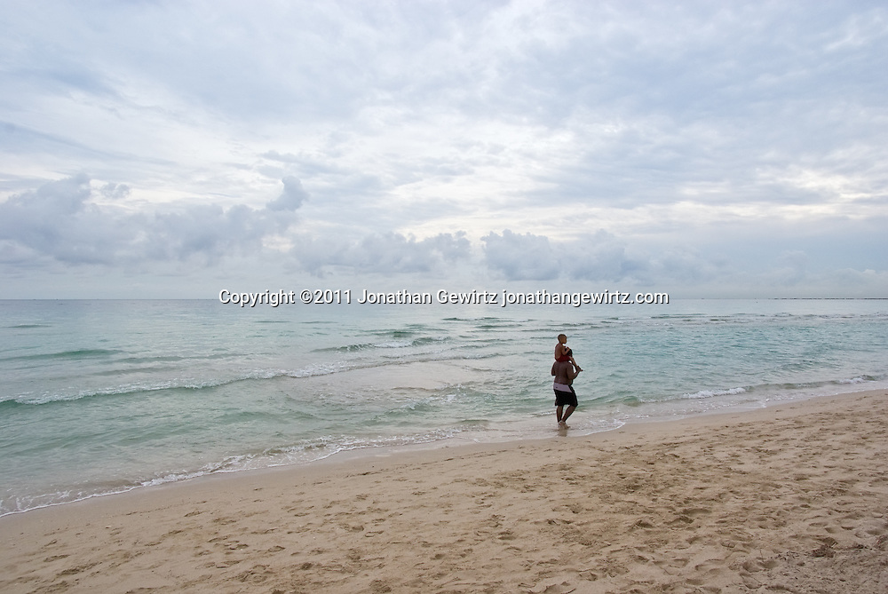 An adult carries a child through the surf on Miami Beach. WATERMARKS WILL NOT APPEAR ON PRINTS OR LICENSED IMAGES.