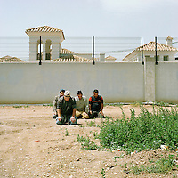 Murcia, Spain. From a story on the explosion of controversial golf resorts in Spain's arid south-east. These walled developments are often built on former farming land when farmers sell their land to the big developers. Most of these new houses are sold to foreign buyers as holiday homes..Photo shows vegetable pickers from Morocco praying near the Polaris World La Torre Golf Resort which is under construction in Murcia, Spain..Photo©Steve Forrest/Amaya Roman