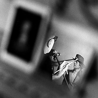 Capitol muralist Cliff Young reflected in a mirror used in his work on the ceiling of a hallway in the U.S. Capitol.