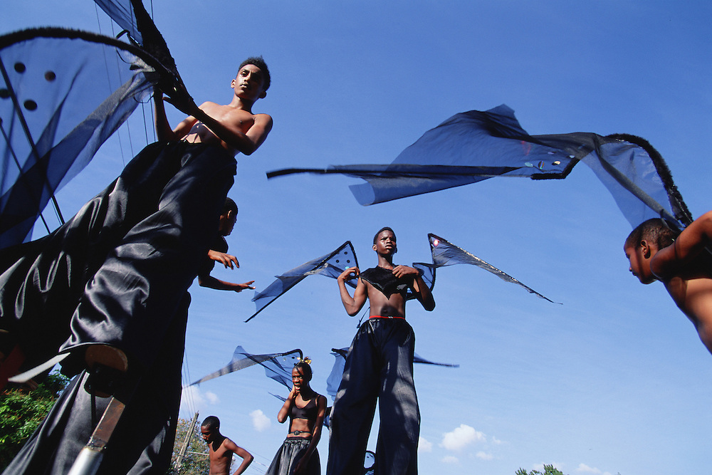"Trinidad and Tobago ""MOKO JUMBIES: The Dancing Spirits of Trinidad"".(Moko Jumbies in self made variations of a traditional Bat costume strike dramatically silhouetted poses at an event in Port of Spain.).A photo essay about a stilt walking school in Cocorite, Trinidad..Dragon Glen de Souza founded the Keylemanjahro School of Art & Culture in 1986. The main purpose of the school is to keep children off the streets and away from drugs..He first taught dances like the Calypso, African dance and the jig with his former partner Cathy Ann Samuel.  Searching for other activities to engage the children in, he rediscovered the art of stilt-walking, a tradition known in West Africa as the Moko Jumbies , protectors of the villages and participants in religious ceremonies. The art was brought to Trinidad by the slave trade and soon forgotten..Today Dragon's school has over 100 members from age 4 and up..His 2 year old son Mutawakkil is probably the youngest Moko Jumbie ever. The stilts are made by Dragon and his students and can be as high as 12-15 feet. The children show their artistic talents mostly at the annual Carnival, which today is unthinkable without the presence of the Moko Jumbies. A band can have up to 80 children on stilts and they have won many of the prestigious prizes and trophies that are awarded by the National Carnival Commission. Designers like  Peter Minshall , Brian Mac Farlane and Laura Anderson Barbata create dazzling costumes for the school which are admired by thousands of  spectators. Besides stilt-walking the children learn the limbo dance, drumming, fire blowing and how to ride  unicycles..The school is situated in Cocorite, a suburb of Port of Spain, the capital of Trinidad and Tobago..all images © Stefan Falke"