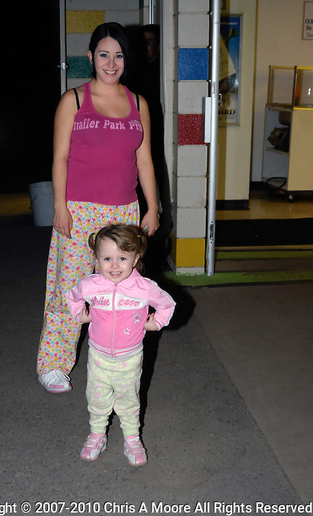 A mother and daughter sporting similar clothing head into the snack bar.  The little girl loved having her photograph taken.