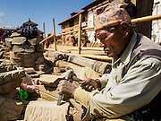 03 MARCH 2017 - BHAKTAPUR, NEPAL: A Nepali craftsman carves stones that will be used in a Hindu temple in the reconstruction of Bhaktapur's Durbur Square. Bhaktapur, a popular tourist destination and one of the most historic cities in Nepal was one of the hardest hit cities in the earthquake. Recovery seems to have barely begun nearly two years after the earthquake of 25 April 2015 that devastated Nepal. In some villages in the Kathmandu valley workers are working by hand to remove ruble and dig out destroyed buildings. About 9,000 people were killed and another 22,000 injured by the earthquake. The epicenter of the earthquake was east of the Gorka district.      PHOTO BY JACK KURTZ