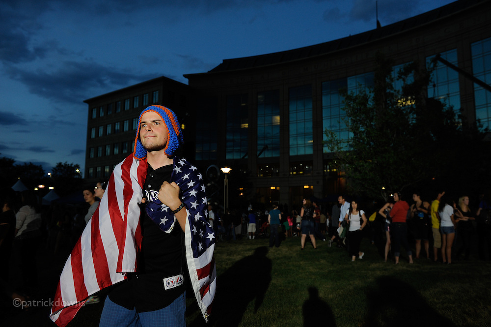 """Aurora, CO: Chris Gibson, 24, of Aurora is wrapped in the US flag in the waning light after the large vigil for the theatre shooting victims. He said, """"I just am thankful for all the heroes and wanted to pay my respects to the victims."""" He said he was friends with and knew both dead victims Veronica Moser-Sullivan and Micayla Medek and some of the wounded."""
