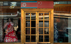 A North Korean waitress is seen in a North Korean restaurant window in Dandong, Liaoning Province, China on 07 April 2013. China on 07 April said its embassy in Pyongyang was still 'operating normally' following North Korea's warning to diplomats that it could only guarantee their safety until Wednesday. Beijing had asked North Korea to protect the safety and interests of Chinese citizens and businesses in the country.