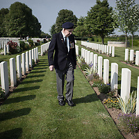 A British veteran searching the grave of one of his fellow soldier that was killed in France in the British cemetery in Bayeux