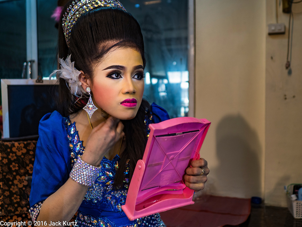 """30 JANUARY 2016 - NONTHABURI, NONTHABURI, THAILAND: A likay performer gets ready for a """"likay"""" show at Wat Bua Khwan in Nonthaburi, north of Bangkok. Likay is a form of popular folk theatre that includes exposition, singing and dancing in Thailand. It uses a combination of extravagant costumes and minimally equipped stages. Intentionally vague storylines means performances rely on actors' skills of improvisation. Like better the known Chinese Opera, which it resembles, Likay is performed mostly at temple fairs and privately sponsored events, especially in rural areas. Likay operas are televised and there is a market for bootleg likay videos and live performance of likay is becoming more rare.     PHOTO BY JACK KURTZ"""