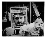 French Maghrebi rises from poster of composite of Al Qaida leader Abu Musab al-Zarqawi and Chechen leader Shamil Bassaev in a Paris Café,  Belleville.