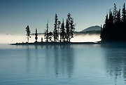 Late summer sunrise at Waldo Lake 1650m with Three Sisters volcanoes beyond; Oregon Cascades