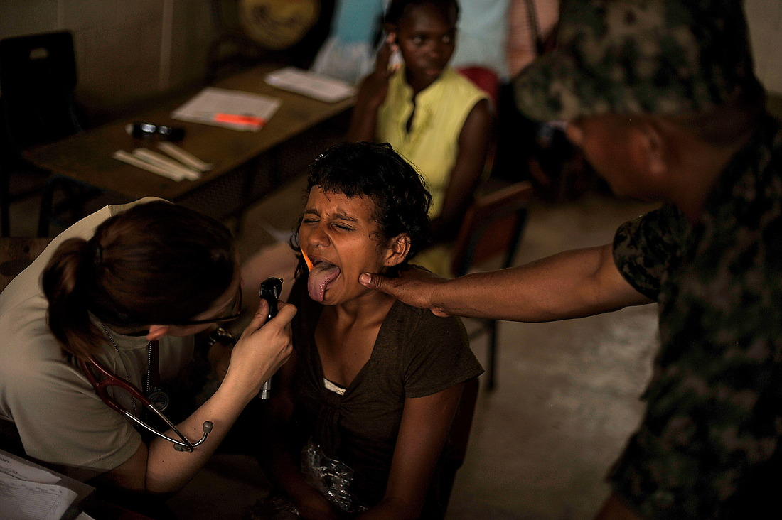 First Lt. Daniela Feldhausen, a physician assistant, checks the mouth of a young Honduran girl from the costal village of Batalla. The young girl complained of a belly ache. — © /
