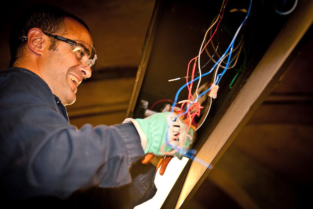 L'électricien Juan Zarate répare des circuits de néon sur le quai de la station Monk.