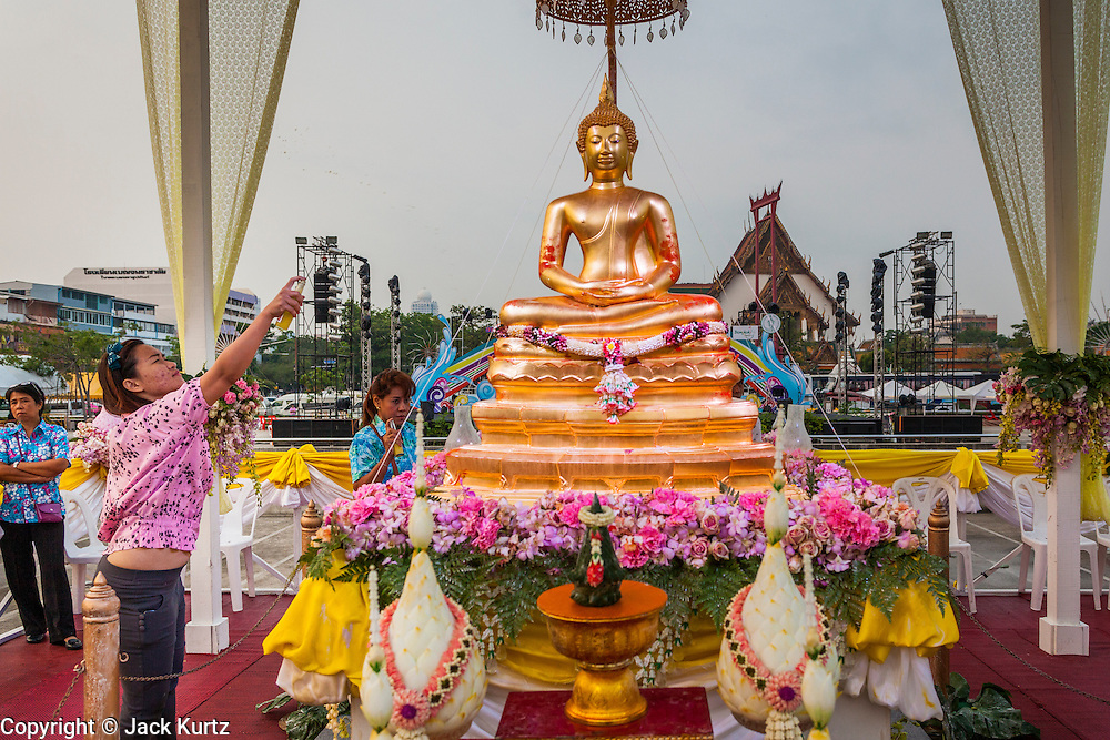 13 APRIL 2014 - BANGKOK, THAILAND:  A woman bathes the Phra Buddha Sihing statue in scented oils at Bangkok City Hall. Many people go to temples and religious ceremonies to make merit on Songkran. Songkran is celebrated in Thailand as the traditional New Year's Day from 13 to 16 April. Songkran is in the hottest time of the year in Thailand, at the end of the dry season and provides an excuse for people to cool off in friendly water fights that take place throughout the country. Songkran has been a national holiday since 1940, when Thailand moved the first day of the year to January 1.   PHOTO BY JACK KURTZ