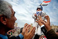 A baby is held out to a crowd of protesters during a Coptic Christian prayer in Tahrir Square in Cairo, February 6, 2011.  Ann Hermes/© The Christian Science Monitor 2011