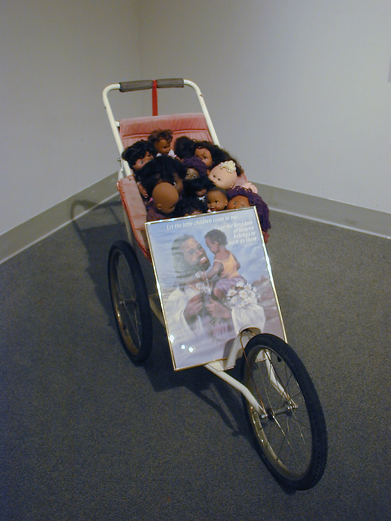 Joe Minter (b. 1943)<br /> <br /> &quot;Jesus Loves the Little Children,&quot; 2000<br /> Baby stroller, dolls, lithograph of Jesus and other found objects, 40 x 22 x 62<br /> <br /> Joe Minter's use of a baby stroller stuffed with worn-out dolls and an old framed print calls to mind the assemblages of contemporary trained artists, who also employ found objects to fashion works of art. The construction's title &quot;Jesus Loves the Little Children&quot; is inspired by a Christian hymn, but Minter's poignant vision creates a metaphor symbolizing the disposability of human life.