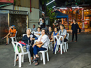 08 DECEMBER 2016 - BANGKOK, THAILAND: Spectators watch a Chinese opera (also called ngiew in Thailand) performance at Pek Leng Keng Shrine in the Khlong Toei neighborhood of Bangkok. Public performances of music and celebration were banned during the first 30 days of the mourning period for Bhumibol Adulyadej, the Late King of Thailand. Now, nearly two months after the revered monarch's death, Bangkok street life is returning to normal and Chinese temples and shrines are once again scheduling operas.      PHOTO BY JACK KURTZ