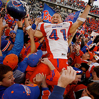 Fans hoist Boise State running back Ian Johnson, holding his helmet in one hand and an empty bag of Tostito's in the other, after the Broncos beat the University of Nevada at Mackay Stadium in Reno, NV.