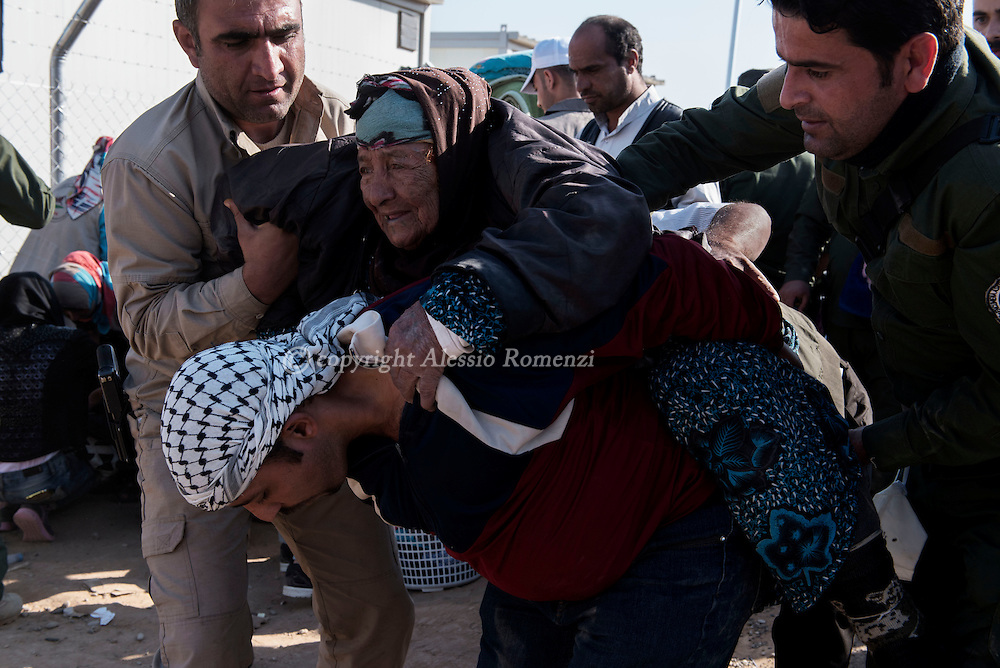 Iraq: as they arrived by truck a man carries an old woman<br /> at the entrance of the Hasan Shame IDP camp in Al Kazir area after fleeing fighting in Mosul on November 5, 2016. Alessio Romenzi