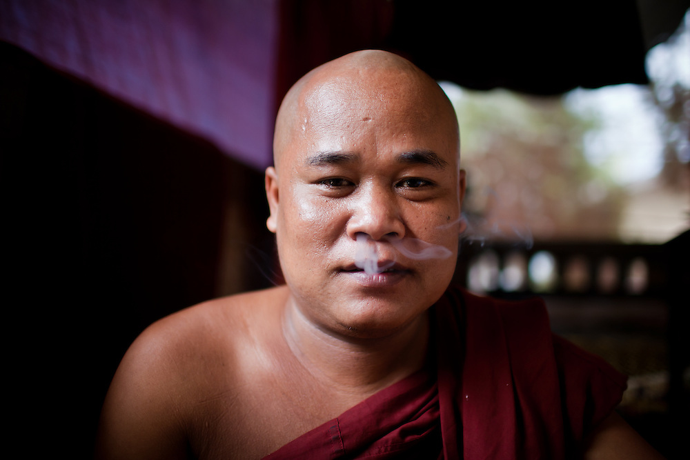 A monk enjoys a ciggarette.