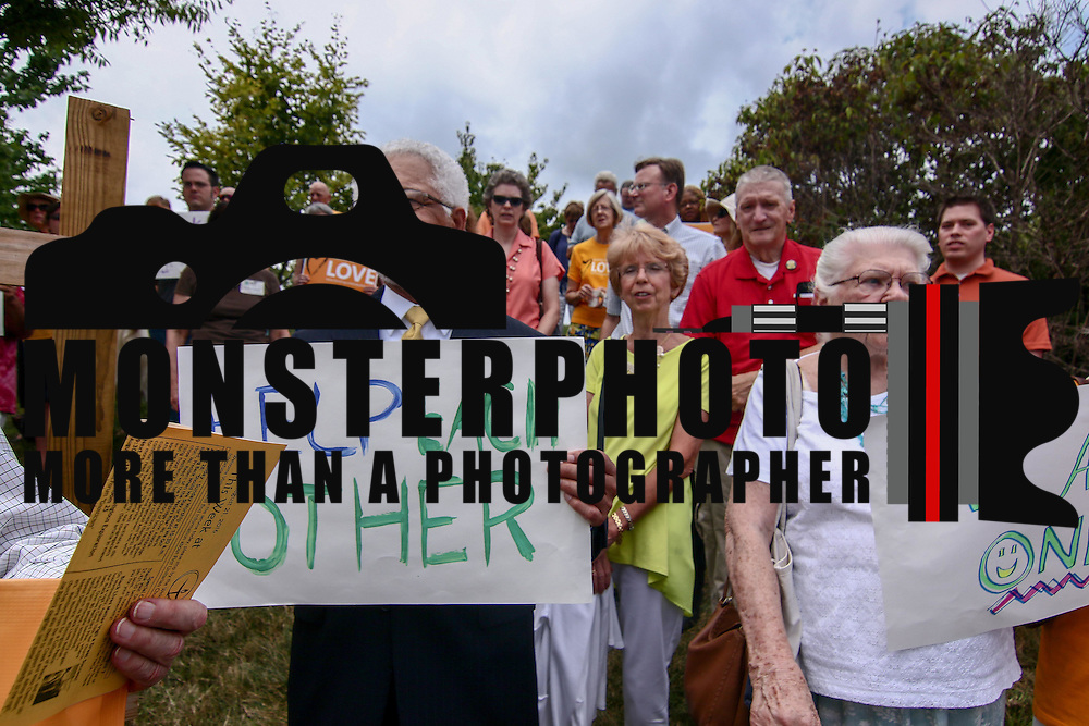 "Retired elected official Theodore ""Ted"" Blunt, Left, holds a sign that reads ""Help Each Other"" during a rededication ceremony Sunday, August 21, 2016, at First Unitarian Church in Wilmington."