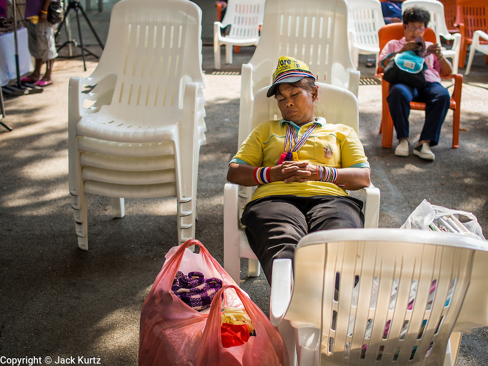 "08 APRIL 2014 - BANGKOK, THAILAND:   A Thai anti-government protestor sleeps at the main protest site in Lumpini Park in Bangkok. Several hundred anti-government protestors led by Suthep Thaugsuban went to the Ministry of Justice in Bangkok Tuesday. Suthep and the protestors met with representatives of the Ministry of Justice and expressed their belief that Thai politics need to be reformed and that corruption needed to be ""seriously tackled."" The protestors returned to their main protest site in Lumpini Park in central Bangkok after the meeting.  PHOTO BY JACK KURTZ"