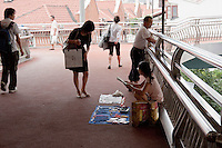 girl sells items on the walkways in Shanghai China