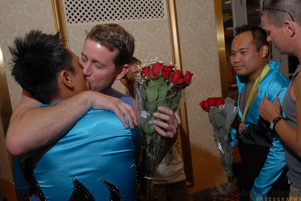 ****EMBARGO: NOT FOR PUBLICATION IN THE ADVOCATE, CURVE, GONYC OR OUT MAGAZINES..Gay ballroom dancers Michaelle Pureza, right, of Westchester, Illinois, and Chip Payos, left of Chicago, Illinois are greeted by their boyfriends after winning a medal in the Dancesport (ballroom dancing) competition at the Hilton Hotel and Towers in downtown Chicago during Gay Games VII on July 19, 2006. ..The boyfriend's greeting them are Gordon Hannon, second from left, and J. Zack. ..Over 12,000 gay and lesbian athletes from 60 countries are in Chicago competing in 30 sports during the Games from July 15 through 22, 2006. ..Over 50,000 athletes have competed in the quadrennial Games since they were founded by Dr. Tom Wadell, a 1968 Olympic decathlete, and a group of friends in San Francisco in 1982, with the goal of using athletics to promote community building and social change. ..The Gay Games resemble the Olympics in structure, but the spirit is one of inclusion, rather than exclusivity. There are no qualifying events or minimum or maximum requirements...The Games have been held in Vancouver (1990), New York (1994), Amsterdam (1998), and Sydney (2002). .
