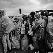 Refugees try to protect themsleves from the rain while waiting for buses in a makeshift camp near Tovarnik's train station, Croatia.<br />