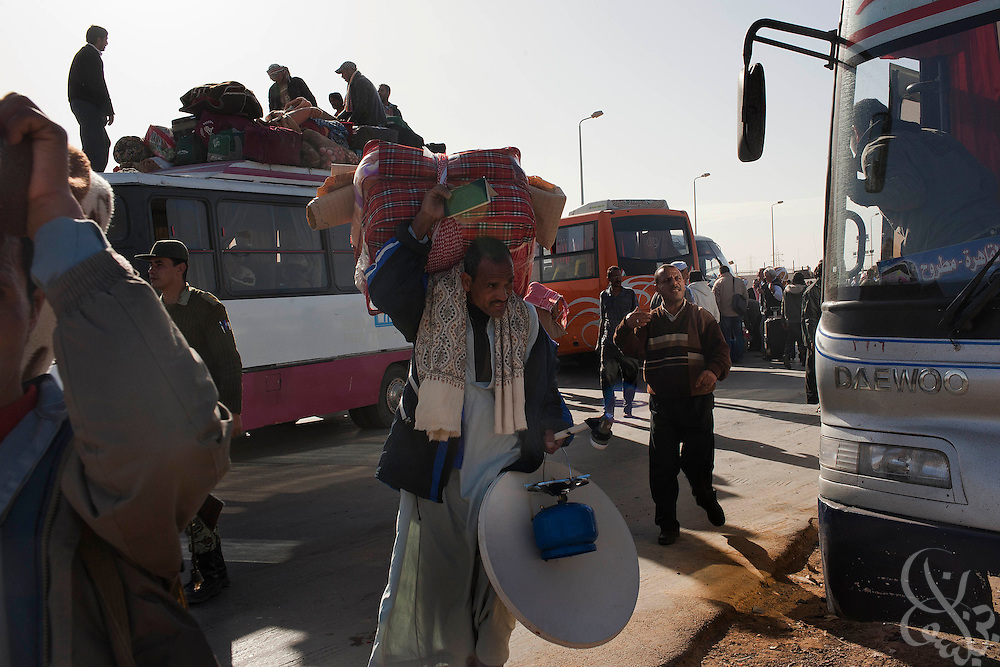 Egyptian workers and families stream across the Egypt-Libya border with thousands of other Egyptians at Saloum, Egypt during ongoing protests and spreading revolution February 22, 2011 in neighboring Libya. .Slug: Libya.Credit: Scott Nelson for the New York Times