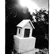 SHOT 11/18/11 3:16:01 PM - A tiny roadside capilla along Highway 109 near Coba, Mexico. Roadside capillas, or tiny chapels, in the Mexican state of Quintana Roo. The capillas are common along the roads and highways of Mexico which is heavily Catholic and are often dedicated to certain patron saints or to the memory of a loved one that has passed away. Often times they contain prayer candles, pictures, personal artifacts or notes. (Photo by Marc Piscotty / © 2011)