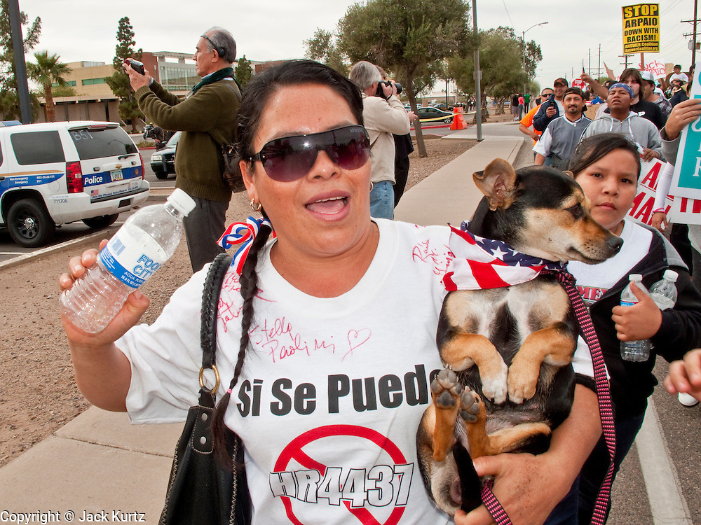 """16 JANUARY 2010 -- PHOENIX, AZ:  Dalia Valdez (CQ) and her dog, Gorda (CQ) march past the jail. About 10,000 people marched the 2.5 miles from Falcon Park to the """"Tent City"""" on Durango to protest against Maricopa County Sheriff Joe Arpaio and his immigration enforcement tactics. PHOTO BY JACK KURTZ"""