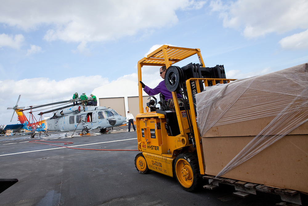 Cargo is shuffled on the flight deck of the USNS Comfort, a naval hospital ship, as HSC 28, a helicopter sea combat detachment out of Norfolk, Virginia, preps a helicopter to transport patients on its mission to help survivors of the earthquake in Haiti on Monday, January 18, 2010 in the Atlantic Ocean off the coast of the United States.