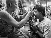 """07 MARCH 2015 - NAKHON CHAI SI, NAKHON PATHOM, THAILAND:  A monk blesses a man by rubbing gold leaf on the man's forehead at the Wat Bang Phra tattoo festival. Wat Bang Phra is the best known """"Sak Yant"""" tattoo temple in Thailand. It's located in Nakhon Pathom province, about 40 miles from Bangkok. The tattoos are given with hollow stainless steel needles and are thought to possess magical powers of protection. The tattoos, which are given by Buddhist monks, are popular with soldiers, policeman and gangsters, people who generally live in harm's way. The tattoo must be activated to remain powerful and the annual Wai Khru Ceremony (tattoo festival) at the temple draws thousands of devotees who come to the temple to activate or renew the tattoos. People go into trance like states and then assume the personality of their tattoo, so people with tiger tattoos assume the personality of a tiger, people with monkey tattoos take on the personality of a monkey and so on. In recent years the tattoo festival has become popular with tourists who make the trip to Nakorn Pathom province to see a side of """"exotic"""" Thailand.   PHOTO BY JACK KURTZ"""