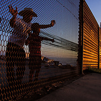 View from another world, a father and son peer through the international boundary into the United States from Tijuana, Mexico.