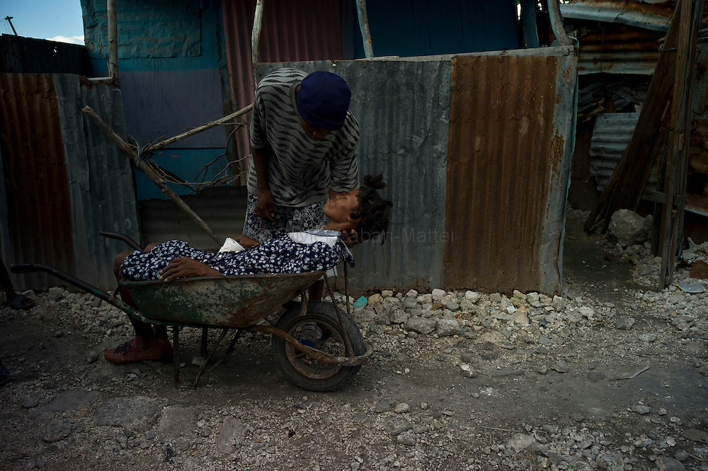 The number of people affected by cholera in Cité Soleil, a slum of Port-au Prince,is increasing day by day exponentially, according to a doctor of Doctors Without Borders.///Jean-Pierre Britus files his mother suffering from cholera, Kernilis St John in a wheelbarrow, in the slum of Cite Soleil in Port-au-Prince, to transport her to St. Catherine's hospital in Cite Soleil.
