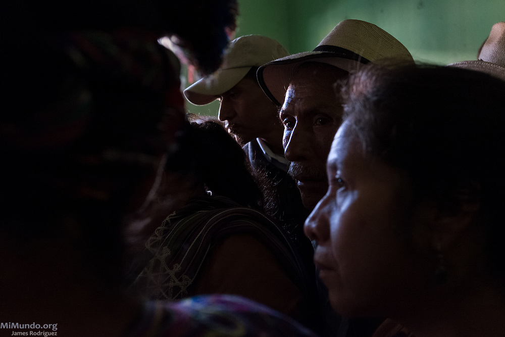 Ixil Mayan residents of Nebaj watch as the human remains of 36 war victims are returned to their surviving family members for a proper burial. Most of the victims, exhumed from mass graves in Xe'xuxcap, near Acul, starved in the mountainside while fleeing State-led repression in 1982. Most of the remains, exhumed by members of the Forensic Anthropology Foundation of Guatemala (FAFG) in 2013, were identified using DNA analysis and buried 35 years after their death. Nebaj, Quiché, Guatemala. February 2, 2017.