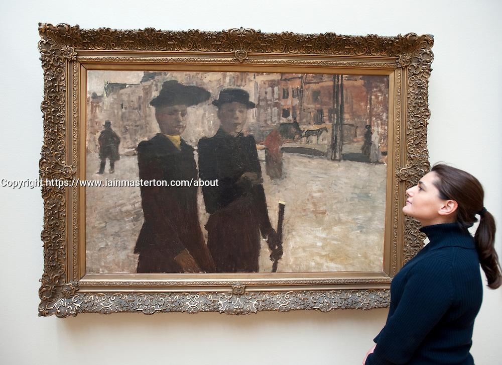 Visitor looking at painting Women in Amsterdam by George Hendrik Breitner at Royal Museum for Fine Arts in Antwerp Belgium