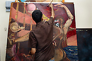 Celebrated young pakistani artist Asim Butt on a journey of political graffiti through Pakistan during the summer of 2009..Asim works on a recent painting in his studio in karachi.