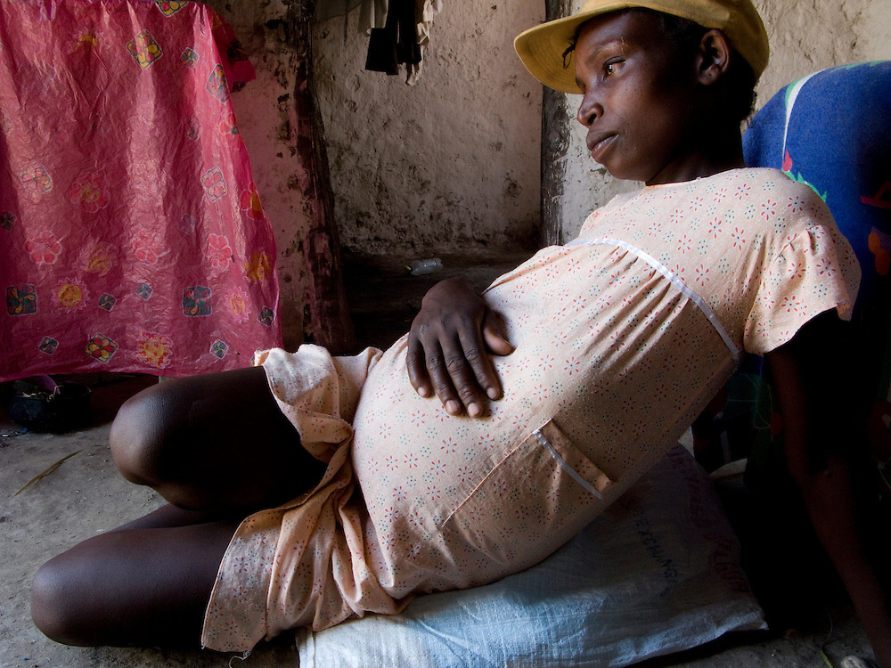 A pregnant woman sits on a pillow in her home.