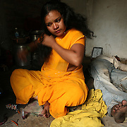 Surekha Kamble brushes her hair in preparation for her evening's work.  Kamble has been a Devadasi sexworker since she was sixteen and  lives in Miraj's redlight district.  Her mother was a Devadasi sexworker and as is tradition, she and her sister too became Devadasis.  She is also a peer educator involved in raising awareness in her community about HIV/AIDS as well as other sexually transmitted diseases.  Her two daughters, Chandrike and Ropani, are both being educated at a residential school for the children of Devadasis and she has hopes that they will not follow her into the Devadasi lifestyle.