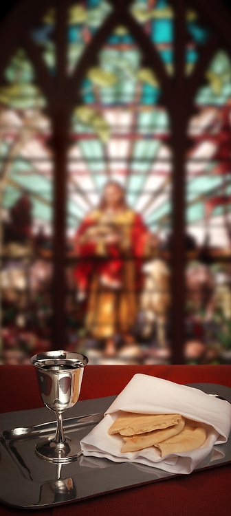 communion chalice and bread with stained glass window in the background