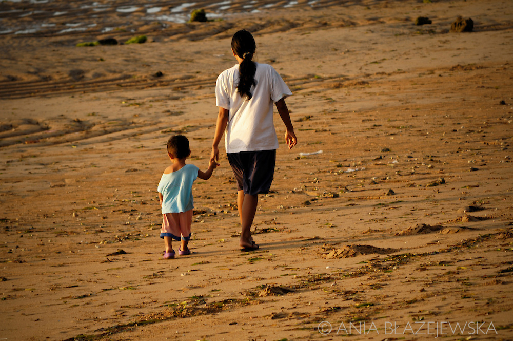 Indonesia, Bali. Mother and a child walking on the beach in Sanur early morning.