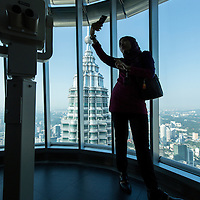 Asia, Malaysia, Kuala Lumpur, Silhouette of young woman taking selfie snapshots of herself at 86th Floor Observation Deck of top of Petronas Towers