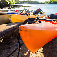 Closeup view of kayaks and canoes beached on a sunny river bank. WATERMARKS WILL NOT APPEAR ON PRINTS OR LICENSED IMAGES.