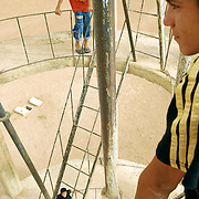 Boys climb a water tower in Melapolat. These boys live in the village year-round, and are among the first generation of Beritan to grow up with electricity and plumbing as a year-round norm.