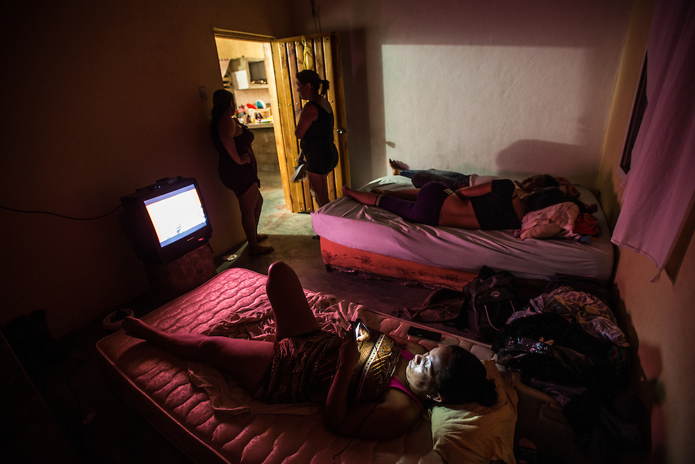 FALCÓN, VENEZUELA - SEPTEMBER 25, 2016: Undocumented migrants spend the night at the safe house while they wait for the smuggler's boat to arrive that will illegally take them from Venezuela to Curaçao. Undocumented migrants here have mortgaged property, sold kitchen appliances and even borrowed money from the same smuggling rings that pack them on the floorboards alongside drugs and other contraband. The journey to Curaçao takes them on a 60-mile crossing filled with backbreaking swells, gangs of armed boatmen and coast guard vessels looking to capture migrants and send them home. Then, after being tossed overboard and left to swim ashore, they hide in the brush to meet contacts who spirit them anew into the tourist economy of this Caribbean island. They clean the floors of restaurants, work in construction, sell trinkets on the street, or even solicit Dutch tourists for sex. But at least, the migrants say, there is food. PHOTO: Meridith Kohut for The New York Times