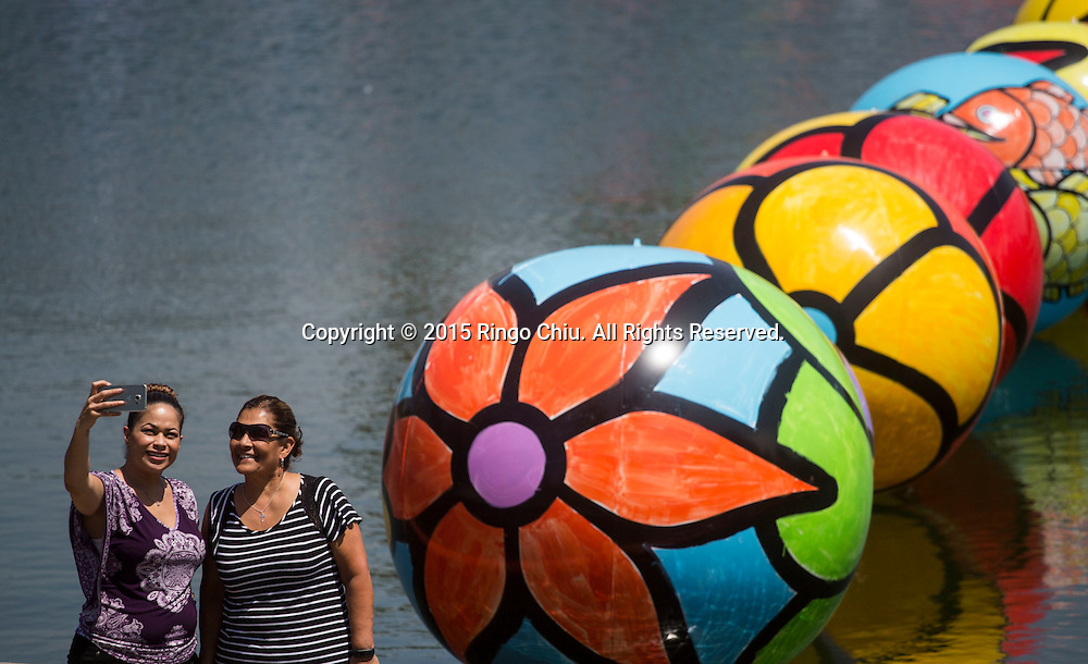 People take photos with the hand-painted vinyl balls floating in the MacArthur Park Lake as part of a large-scale public arts installation organized by the Portraits of Hope charity in Los Angeles, California on August 26, 2015. The work titled ``The Spheres at MacArthur Park,'' involves filling the park's 8.39-acre lake with about 3,000 balls, each 4 to 6 feet in diameter and covered in bright floral and fish patterns. (Photo by Ringo Chiu/PHOTOFORMULA.com)
