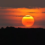 "The orange sun sets in the Galápagos Islands, Ecuador, South America. In 1959, Ecuador declared 97% of the land area of the Galápagos Islands to be Galápagos National Park, which UNESCO registered as a World Heritage Site in 1978. Ecuador created the Galápagos Marine Reserve in 1998, which UNESCO appended in 2001. Published in Martin Dawe Design company calendar 2013, UK. Published in ""Light Travel: Photography on the Go"" book by Tom Dempsey 2009, 2010."