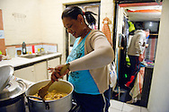 MANENBERG, SOUTH AFRICA - SEPTEMBER 26: Roegchanda Pascoe checks on a curry dinner in her kitchen as she cooks for her family and for anyone in the neighborhood in need of food on September 26, 2013 in Manenberg, a township of Cape Town, South Africa. Pascoe works at the Manenberg People's Centre, one of the few safe havens in a township that is plagued by drugs and gang violence. Photo by Ann Hermes/The Christian Science Monitor