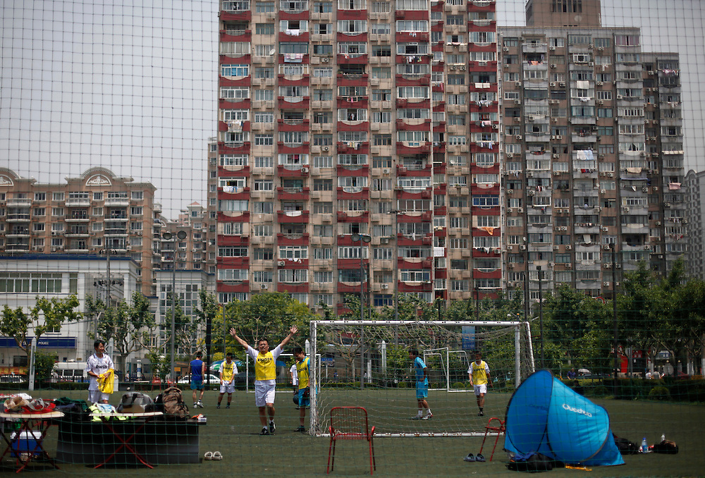 Chinese play football in a green area set against the back drop of apartment buildings in Shanghai, China, Saturday, May 30, 2009. Block after city block, towers of concrete, steel and glass fill the skyline. .Teeming and congested, the intensely urban landscapes of China's biggest cities show a glimpse of what the future will hold for the rest of the country.In the sprawling megacities of Beijing, Shanghai and Chongqing, where populations exceed 10 million people, extreme urban density means that the number of people living within a few square blocks here is equal to the population of entire mid-size U.S. cities. .China's urban population soared to 607 million people last year _ nearly equaling the 700 million living in the countryside. The country's headlong plunge toward urbanization continues unabated as tens of millions of migrants from the countryside flood to cities in search of money, jobs and other opportunities.